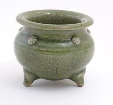 """A Chinese three footed censor with a crackle glaze and floral roundels in relief. Approx. 3 1/4"""""""