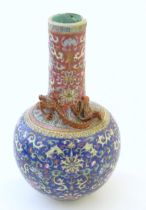 A Chinese bottle vase with scrolling floral and foliate detail, and applied dragon decoration to
