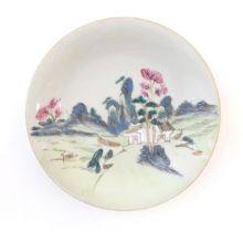 A Chinese plate decorated with a landscape scene with a boat on a river. With red foliate motifs