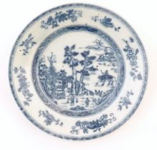 A Chinese blue and white plate depicting a landscape scene with figures, trees, pagodas etc. with