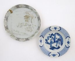 A Chinese blue and white plate decorated with two figures in a landscape scene, the border with