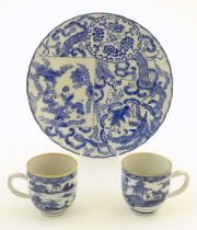 An Oriental blue and white plate decorated with figures and scrolling flowers and foliage. With blue