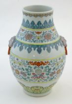 A Chinese famille verte vase with a bulbous body with twin ring mask handles, decorated with