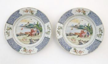A pair of Chinese plates depicting a two figures in a garden watching a bat, with sea and