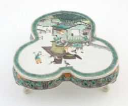 A Chinese famille verte stand of trefoil form depicting figures sifting grain and shooing