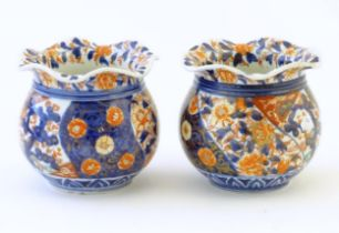Two Oriental vases of bulbous form with flared rims decorated in the Imari palette with flowers