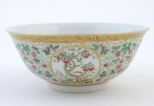 A Chinese famille verte bowl decorated with fruiting trees and landscapes scenes in roundels and