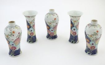 Five Chinese famille rose vases comprising two trumpet vases with floral and foliate detail, and