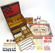 Toys: A late 19th / early 20thC mahogany games box / compendium with two tier fitted interior