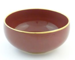 """A Japanese bowl with a red glaze and gilt rim. Character marks under. Approx. 4"""" high x 8 1/2"""""""