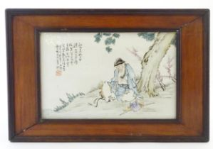 A Chinese porcelain plaque decorated with a seated elder / scholar beneath a tree, with Oriental