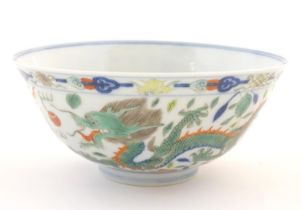 A Chinese bowl with dragon and flaming pearl detail, with flowers, foliate and stylised clouds.