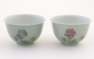 A pair of Chinese tea bowls decorated with flowers and Oriental script. Character marks under.