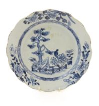 A Chinese blue and white plate with a lobed rim decorated with a landscape scene with trees and