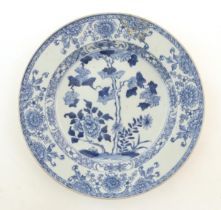 A Chinese blue and white plate decorated with flowers and foliage. With stylised motifs to
