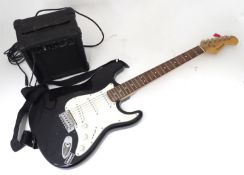A Burswood stratocaster type guitar with small amplifier, leads, bag, etc. Please Note - we do not