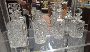 A SQUARE-FORM CUT GLASS DECANTER, and three others