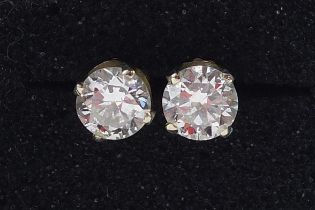 Pair of 14ct gold diamond solitaire earrings, each approximately 5.5mm in diameter x 3.5mm deep