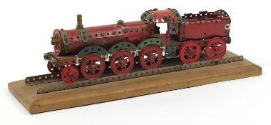 Vintage Meccano scratch built locomotive raised on a rectangular wood plinth base, 63cm wide :