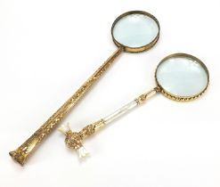 Two large antique gilt metal magnifying glasses including one with mother of pearl handles, the
