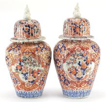 Large pair of Japanese Imari lidded porcelain vases, each profusely hand painted with flowers,