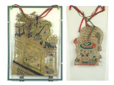 Two Chinese vellum theatre shadow puppets of dragons, each housed in a glass hanging frame, the