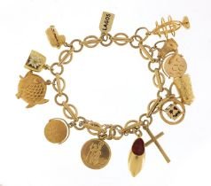 9ct gold charm bracelet with a selection of mostly gold charms including St Christopher, Dutch