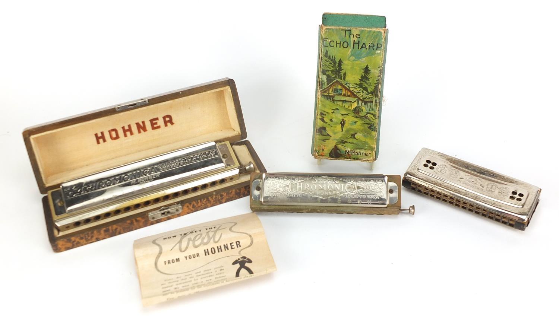 Three vintage harmonicas including The 64 Chromonica by Hohner, Super Chromonica by Hohner and