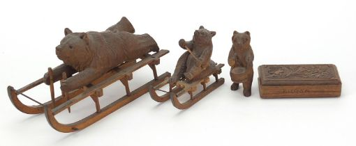 Three carved Black Forest bears and a matchbox including two riding sleds, the largest 15cm in