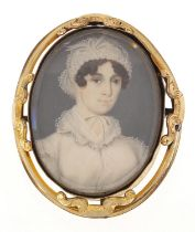 Oval hand painted portrait miniature of a female in Georgian dress housed in a gilt metal brooch