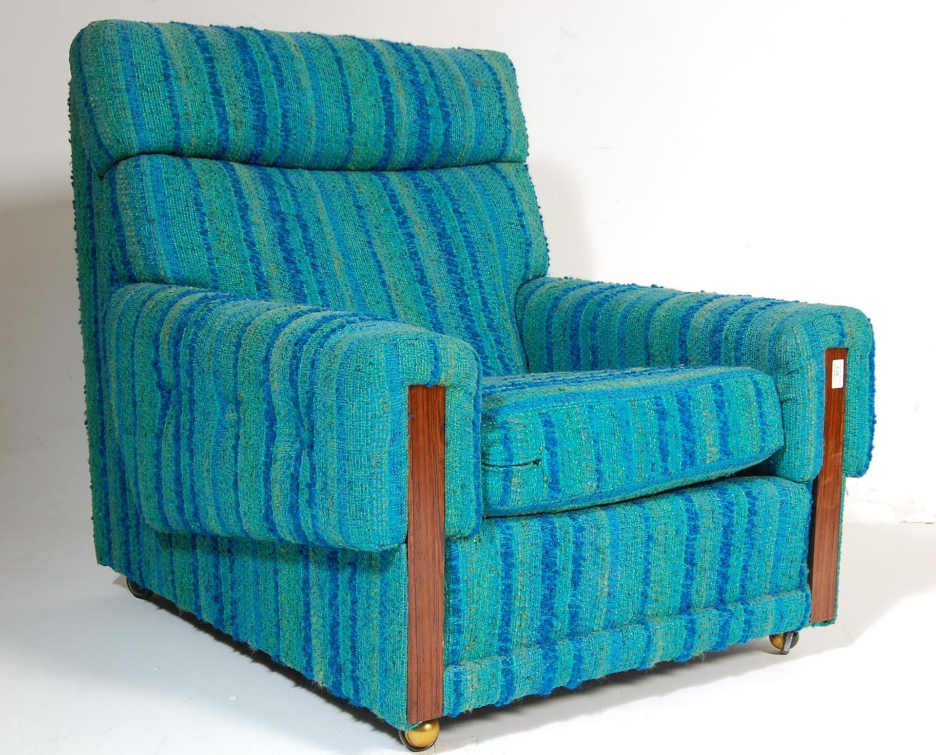 A retro mid century teak wood and upholstered easy chair / armchair
