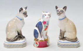 THREE CAT FIGURINES BY ROYAL WORCESTER AND HALCYON DAYS TO INCLUDE THE SIAMESE CAT AND GILES CAT.