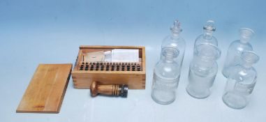 EARLY 20TH CENTURY EDWARDIAN POST OFFICE METAL STAMPERS AND SIX CHEMISTRY GLASS BOTTLES
