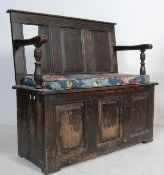 A 17TH CENTURY CARVED OAK HALL SETTLE BENCH.
