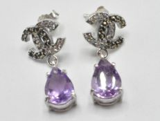 A pair of silver crossed C earrings set with pear cut amethyst drops, with marcasite's and white