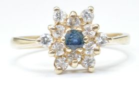 9CT GOLD BLUE AND WHITE STONE FLOWER HEAD RING