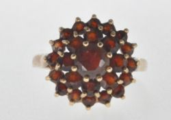 STAMPED 375 9CT GOLD AND RED STONE CLUSTER RING.