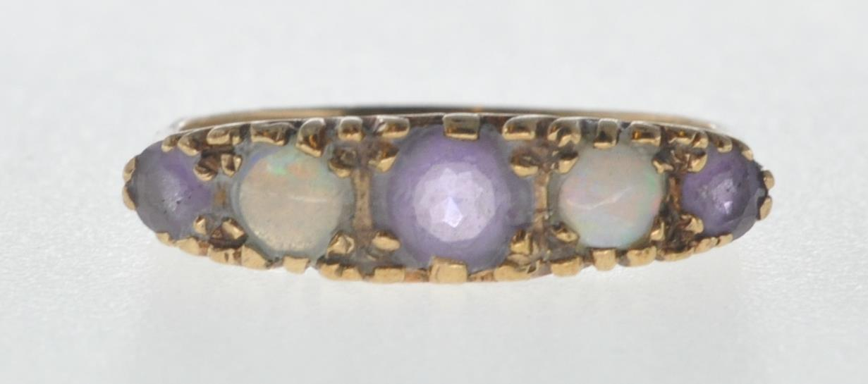 9CT GOLD RING SET WITH OPAL CABOCHONS AND PURPLE STONES.