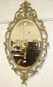 A modern gilt metal bevel-edged oval wall mirror with foliate surround, 127 x 70cm overall.