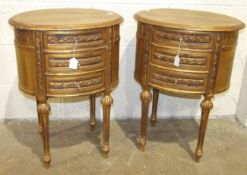 A pair of gilt-painted wood oval bedside tables in the French taste, each fitted with three