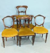 A set of four Victorian balloon-back dining chairs with carved backs, on octagonal turned legs and
