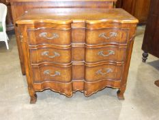 A Continental reproduction stained pine serpentine chest of three long drawers, 117cm wide, 94cm