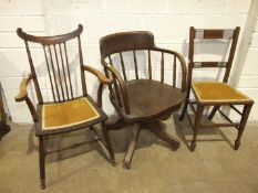 An early 20th century oak office swivel chair on four supports, a wooden armchair and a bedroom