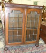 A mid-20th century oak bookcase, the rectangular top above a pair of leaded glass doors on bun feet,