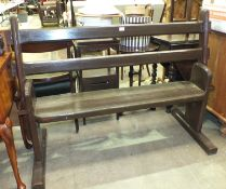 A 20th century stained wood station bench, with moveable back rest to allow seating on either