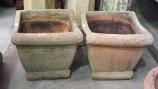 A pair of terracotta-coloured pottery square-form planters, 44cm high, 47cm square, (2).