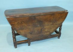 An antique oak drop-leaf dining table, the oval top above an end frieze drawer, on bobbin-turned