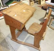 An early 20th century pitch pine and elm school desk and chair, the desk with sloping hinged lid and