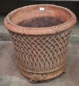 A modern terracotta planter decorated with lattice work, on foliate feet, 52cm high, 54cm diameter.