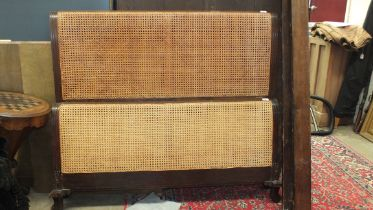 A 4' 6'' mahogany Bergère bed and side rail, with double-caned foot and single-caned head boards, (